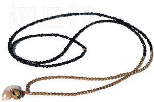 Handgemaakte ketting van kleine goudkleurige koperen kralen en zwarte opaak glaskralen met een parelmoeren knoopje, een koperen belletje en een zoetwaterparel aan een leren koordje.