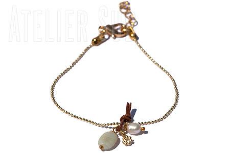 Dun zilverkleurig armbandje met een edelsteentje en een pareltje