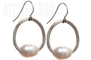 Handgemaakte oorbellen van geborsteld zilver en een 'unshaped' parel