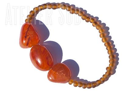 Handgemaakte armband op elastiek van matglas kraaltjes, met drie Carneool stenen.