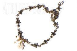 Verguld schakel-armbandje van sterretjes met twee kleine pareltjes, een parelmoeren sterretje en een verstelbare sluiting.