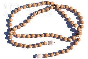 Handgemaakte ketting van gebleekte naturel houten kraaltjes aan een geknoopt koord met aan de uiteinde twee 'unshaped' parels.