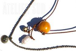 Handgemaakte dubbele ketting. Aan een leren koordje een grote gele Marokkaanse kraal