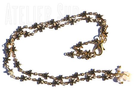 Verguld schakelkettinkje van sterretjes met twee pareltjes, een parelmoeren sterretje en een verstelbare sluiting.