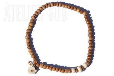 Handgemaakte armband op elastiek met naturel houten kraaltjes een parelmoertje en een pareltje.